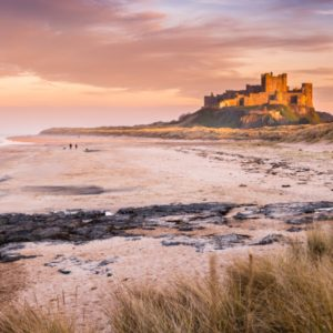 Bamburgh Castle on the Northumberland coastline, bathed in late afternoon golden sunlight